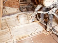 Worker applying spray foam insulation in new construction building